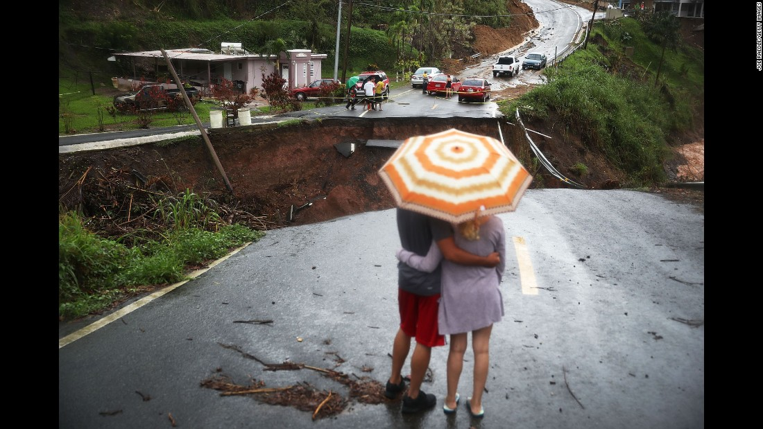 "People look at a collapsed road in Barranquitas, Puerto Rico, on Saturday, October 7. The island <a href=""http://www.cnn.com/interactive/2017/09/world/hurricane-maria-puerto-rico-cnnphotos/"" target=""_blank"">suffered widespread damage</a> from Hurricane Maria."