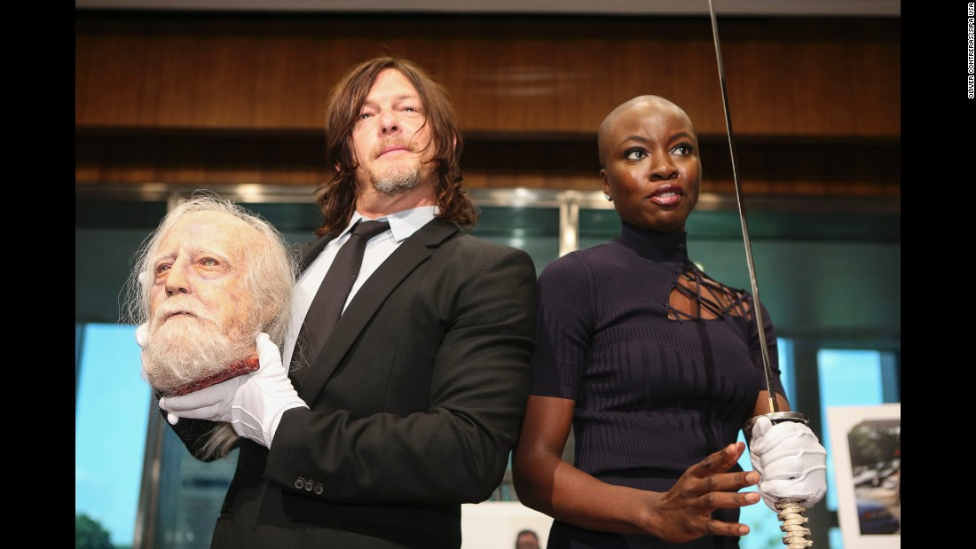 "Actors Norman Reedus and Danai Gurira hold some of ""The Walking Dead"" memorabilia that was donated Tuesday, October 10, to the National Museum of American History. The hit television show will air its 100th episode when the new season premieres on October 22."
