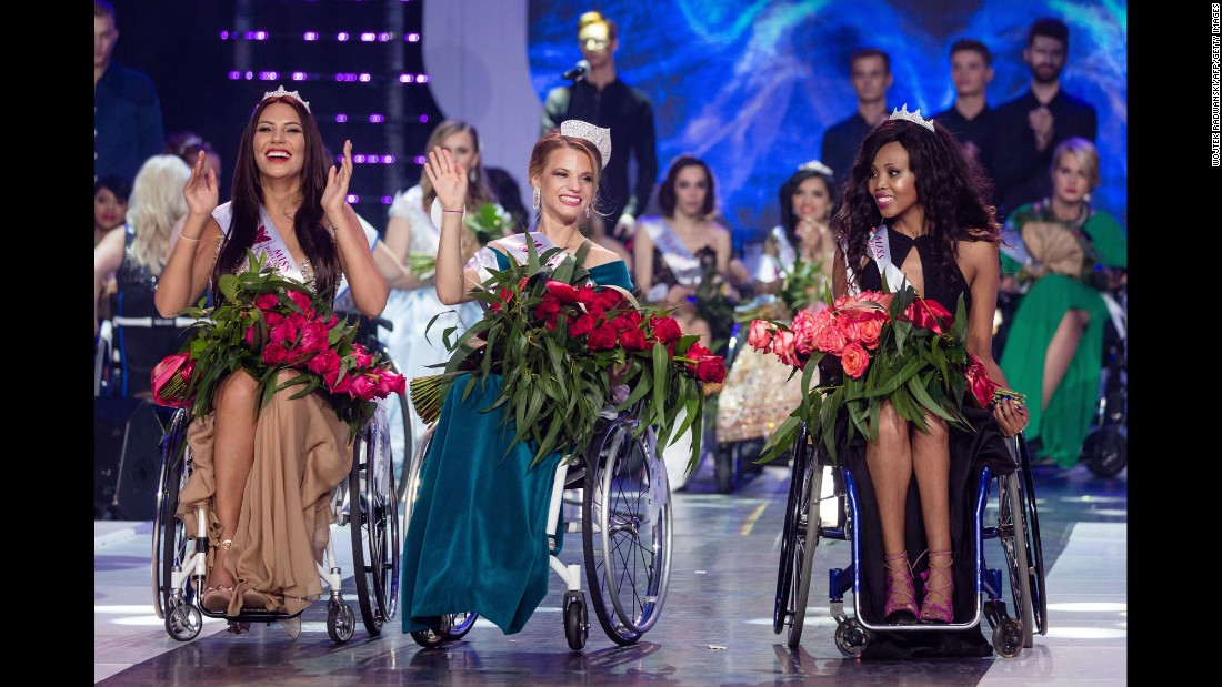 Miss Belarus Aleksandra Chichikova waves to the crowd in Warsaw, Poland, after winning the Miss Wheelchair World beauty pageant on Saturday, October 7. She is flanked by Poland's Adriana Zawadzinska, left, and South Africa's Lebohang Monyatsi.