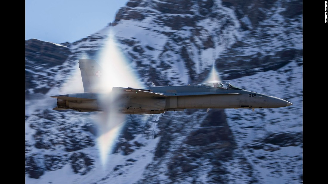 A vapor cone is seen behind a Swiss Air Force jet as it breaks the sound barrier during a demonstration in the Swiss Alps on Tuesday, October 10.