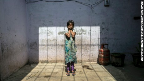 A child rape survivor stands in her home, in Uttar Pradesh, India, 2016.
