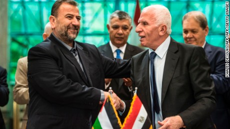 Fatah's Azzam al-Ahmad (R) and Saleh al-Aruri (L) of Hamas shake hands after signing a reconciliation deal in Cairo.