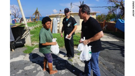 Dr. Humberto Guzman checks on a woman in the Del Negro neighborhood of Yabucoa as a volunteer delivers her food and water.