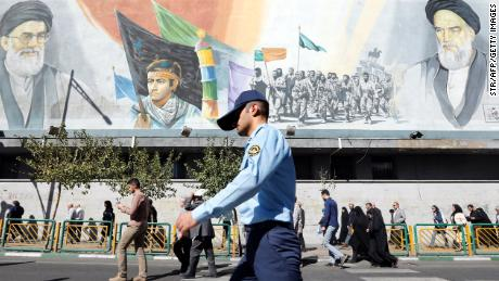 A member of the Iranian army walks past pictures of Ayatollah Ali Khamenei (top left) and of late Supreme Leader Ayatollah Ruhollah Khomeini (top right), in Tehran on October 13.