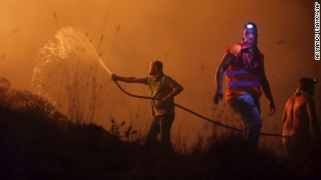 Volunteers use a water hose to fight a wild fire raging near houses in the outskirts of Obidos, Portugal, in the early hours of Monday, Oct. 16 2017. At least six people were killed Sunday as hundreds of forest fires spread across Portugal fueled by high temperatures, strong winds and a persistent drought. (AP Photo/Armando Franca)