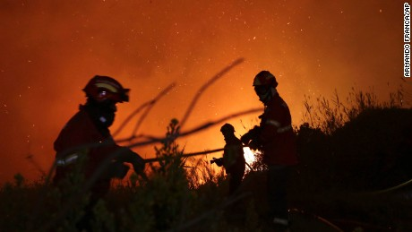 Firefighters battle a wild fire raging near houses on the outskirts of Obidos, Portugal, in the early hours of Monday, Oct. 16 2017. Hundreds of forest fires spread across Portugal fueled by high temperatures, strong winds and a persistent drought. (AP Photo/Armando Franca)
