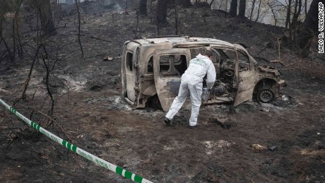 A Police scientist inspects the remains of the car where two women died after a wild fire in Pontevedra, in the northwestern Spanish region of Galicia, Spain, Monday, Oct. 16, 2017. Authorities in Portugal and Spain say that hundreds of wildfires fanned by strong winds have caused multiple deaths as people got trapped by fast moving fires. (AP Photo/Lalo R. Villar)