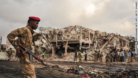 Somali soldiers patrol the scene of the explosions in the center of Mogadishu.