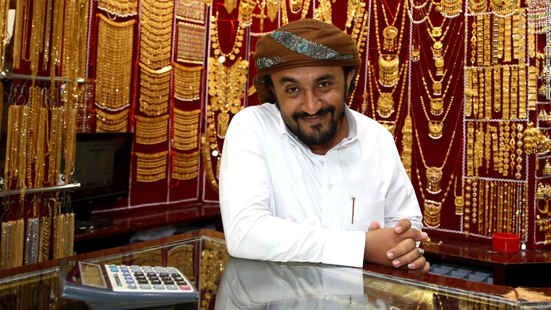 A gold merchant poses with his jewelry at the Dubai Gold Souk. In the lead up to the Indian wedding season traders experience a spike in demand as soon-to-be-weds and their families buy gold jewelry for the occasion.
