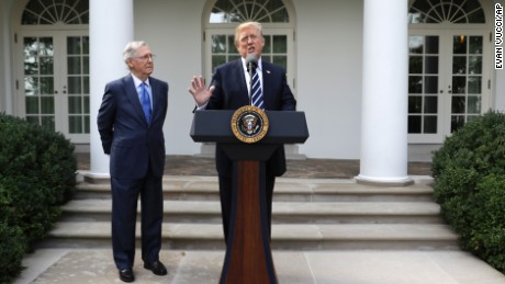President Donald Trump speaks as Senate Majority Leader Mitch McConnell listens in the Rose Garden at the White House on October 16, 2017.
