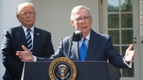 US President Donald Trump listens to Senate Majority Leader Mitch McConnell (R), Republican of Kentucky, speak to the media in the Rose Garden of the White House in Washington, DC, October 16, 2017.