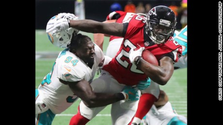 Atlanta Falcons running back Tevin Coleman knocks off Miami Dolphins linebacker Lawrence Timmons' helmet as he breaks the tackle to run for a touchdown during the second half of an NFL football game on Sunday, October 15,  in Atlanta.