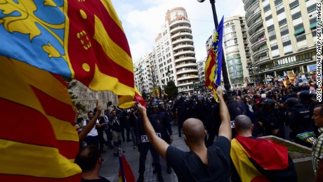 A right-wing nationalist waves Valencia City flags opposite Spanish police forces separating nationalists from a counter demonstration in support of Catalan independence in Valencia on October 9, 2017. Catalan leaders came under intense domestic and international pressure to halt plans to break away from Spain as the clock ticked down to a regional parliamentary session where Catalonia's president could declare independence. / AFP PHOTO / JOSE JORDAN        (Photo credit should read JOSE JORDAN/AFP/Getty Images)