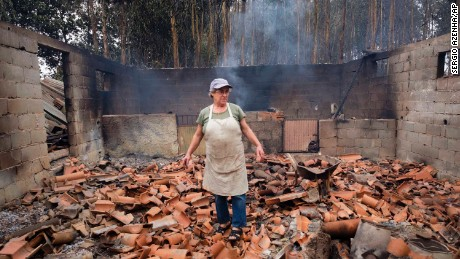 Inocencia Rodrigues, 64, walks among the debris of the burnt shed where she raised chickens and pigs in the village of Sao Joaninho in northern Portugal.