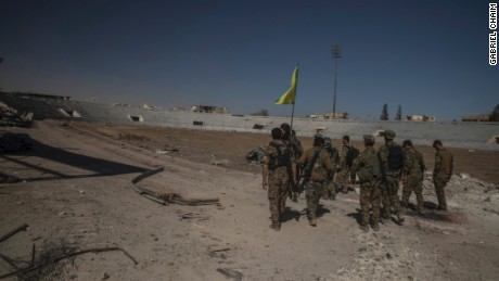 Soldiers of SDF reaching inside of stadium to put the flag.