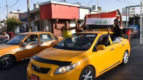 Some residents celebrate after Iraqi forces took control of Kirkuk on Monday.