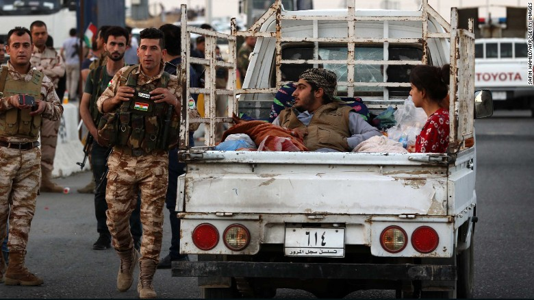 Kirkuk residents cross a Kurdish checkpoint in Altun Kupri on Monday.