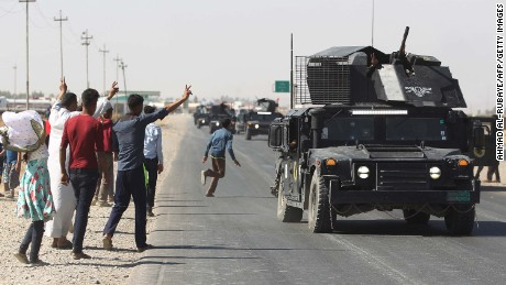Locals wave to Iraqi forces as they arrive in southern Kirkuk on Monday.