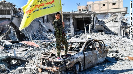 "A member of the Syrian Democratic Forces (SDF), backed by US special forces, holds their flag at the iconic Al-Naim square in Raqa on October 17, 2017. US-backed forces said they had taken full control of Raqa from the Islamic State group, defeating the last jihadist holdouts in the de facto Syrian capital of their now-shattered ""caliphate"". / AFP PHOTO / BULENT KILIC        (Photo credit should read BULENT KILIC/AFP/Getty Images)"