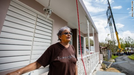 Diana Aponte stands by her home in Aguas Buenas, next to the reconstruction of a transmission tower.