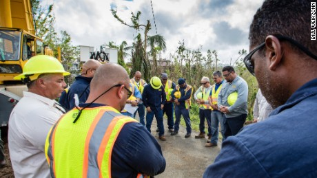 A team working to restore power lines prays by a transmission tower they are getting back up in Aguas Buenas, Puerto Rico.