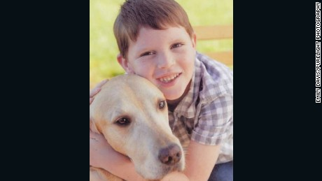 Caden Higuera hugs Larry, a service dog for the Anova Center for Education