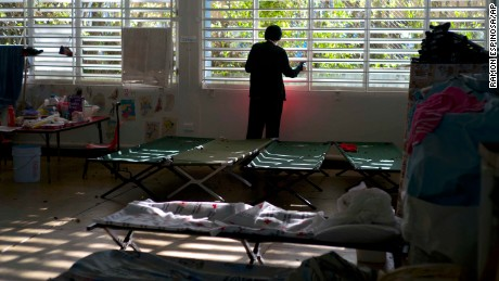 In this Thursday, Oct. 12, 2017 photo, a teenager left homeless by Hurricane Maria looks out the window of the school-turned-shelter where he's living in Toa Baja, Puerto Rico. Many schools on the island are functioning as temporary shelters for those affected by Hurricane, delaying student's education. (AP Photo/Ramon Espinosa)