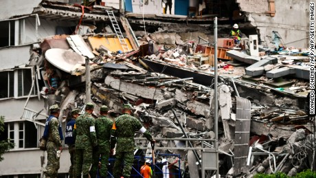 TOPSHOT - Rescuers search for survivors amid the rubble from a building flattened by the 7.1-magnitude quake the day before, in Mexico City, on September 20, 2019.   Rescuers frantically searched Wednesday for survivors of a powerful earthquake that killed more than 200 people in Mexico on the anniversary of another massive quake that left thousands dead and still haunts the country. / AFP PHOTO / RONALDO SCHEMIDT        (Photo credit should read RONALDO SCHEMIDT/AFP/Getty Images)