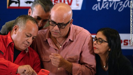 Jorge Rodriguez, mayor of Libertador municipality in Caracas and leader of the pro-government United Socialist Party of Venezuela (2-R), member of the Constituent Assembly Diosdado Cabello (L), Venezuelan Vice-President Tareck El Aissami (2-L) and president of the loyalist-packed Venezuelan Constituent Assembly, Delcy Rodriguez, look at Cabello's cellphone before delivering a press conference, as they wait for the results of the regional elections at the ruling party campaign headquarters in Caracas on October 15, 2017. Millions of Venezuelans voted peacefully in regional elections on Sunday following months of violent protests earlier this year aimed at unseating President Nicolas Maduro. No official turnout figures were available, but an electoral commission source estimated turnout at around 60 percent.  / AFP PHOTO / FEDERICO PARRA        (Photo credit should read FEDERICO PARRA/AFP/Getty Images)