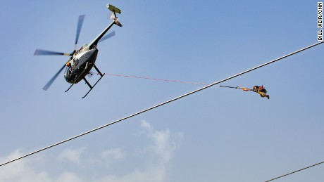 A helicopter hoists workers to fix power lines in Puerto Rico's mountains.