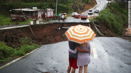 BARRANQUITAS, PUERTO RICO - OCTOBER 07:  People look on at a section of a road that collapsed and continues to erode days after Hurricane Maria swept through the island on October 7, 2017 in Barranquitas, Puerto Rico. Puerto Rico experienced widespread damage including most of the electrical, gas and water grid as well as agriculture after Hurricane Maria, a category 4 hurricane, passed through.  (Photo by Joe Raedle/Getty Images)