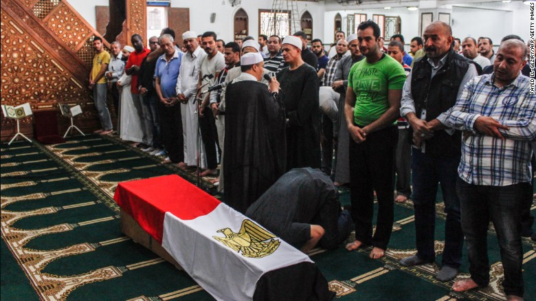 Mourners in Cairo pray during a funeral Saturday for a police captain killed in the desert shootout.