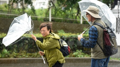 A woman have an umbrella turned inside out with strong wind in Tokyo on October 22, 2017.  A powerful typhoon barrelled toward Japan on October 22, with heavy rain triggering landslides and delaying voting at one ballot station as millions struggled to the polls for a national election.