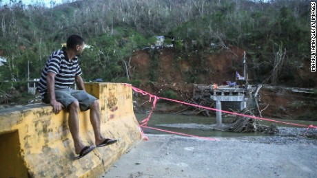 A man sits on the edge of a broken bridge spanning the Vivi River on October 20, 2017 in Utuado, Puerto Rico. The bridge was washed away during Hurricane Maria and ladders descending from the other side are the only way for members of the cut-off Rio Abajo community to access the rest of Utuado municipality. Residents cannot wade across the river because it is contaminated with human waste after a sewer pipe broke during the storm. Residents have rigged up the system of pulleys to manuever supplies across the river to their isolated community. The 27 families in the community have no grid electricity or running water. Today is the one month anniversary of Hurricane Maria.