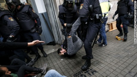 Spanish police officers try to disperse voters at a polling station in Barcelona on October 1.