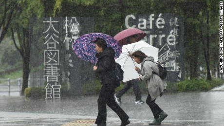 Pedestrians walk along a street under the rain in Tokyo on October 22, 2017.   A powerful typhoon barrelled toward Japan on October 22, with heavy rain triggering landslides and delaying voting at one ballot station as millions struggled to the polls for a national election.  / AFP PHOTO / Kazuhiro NOGI        (Photo credit should read KAZUHIRO NOGI/AFP/Getty Images)