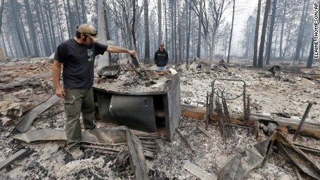 Adam Bailey, left, looks through the still smoldering remains of his home as his father-in-law Joel Miller looks on Monday, Sept. 14, 2015, in Cobb, Calif. Bailey escaped the flames with his baby Saturday, just before flre roared through the neighborhood of about two dozen homes. Two of California's fastest-burning wildfires in decades overtook several Northern California towns, killing at least one person and destroying hundreds of homes and businesses and sending thousands of residents fleeing highways lined with buildings, guardrails and cars still in flames. (AP Photo/Elaine Thompson)