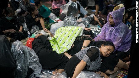 BANGKOK, THAILAND - OCTOBER 24:  People take cover from torrential rain as they begin to queue and sleep on the streets overnight to attend Thailand's late King Bhumibol Adulyadej's cremation and funeral ceremony at the Royal Palace on October 24, 2017 in Bangkok, Thailand. The world's longest serving monarch King Bhumibol Adulyadej died on October 13, 2016. Rehearsals for the five day funeral of the much loved king are taking place around Bangkok's Grand Palace. The ceremonies will take place over five days culminating in the cremation of the king's body in a grand Royal Crematorium on October 26th.  (Photo by Christopher Furlong/Getty Images)