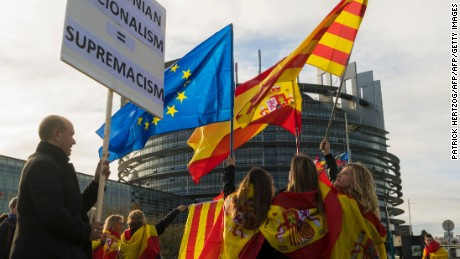 "Women hold Spanish, Catalan and European flags during a demonstration against Catalonia's independence in front of the European Parliament building in Strasbourg, eastern France, on October 24, 2017. Catalan separatists prepare to announce plans on October 24 for a campaign of ""civil disobedience"" in defiance of Madrid's threat to take control of the region as its leaders threaten to declare independence. / AFP PHOTO / PATRICK HERTZOGPATRICK HERTZOG/AFP/Getty Images"