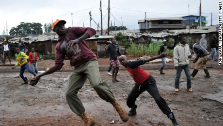 Residents throw stones towards Kenyan police officials as they clash at Katwekera village within Kibera slum - a stronghold of opposition leader Raila Odinga - in Nairobi on October 26, 2017, as voting in Kenya's repeat presidential poll kicked off on a low turn-out at polling stations in the slum.  Kenyan police clashed with opposition protesters in parts of Nairobi and in the west of the country who tried to block voting  in an election boycotted by their leader Raila Odinga, AFP correspondents said. In several western towns, protesters blocked roads and barricaded the entrances to polling stations, lobbing rocks at police who fired teargas to disperse them. In the slums of the Kenyan capital, police also engaged in running battles with residents trying to prevent voting.  / AFP PHOTO / TONY KARUMBA        (Photo credit should read TONY KARUMBA/AFP/Getty Images)