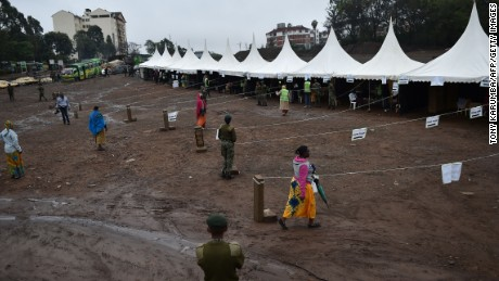 A Kenyan police official looks on as residents walk into a virtually empty polling station Kibera slum - a stronghold of opposition leader Raila Odinga - in Nairobi on October 26, 2017, as voting in Kenya's repeat presidential poll kicked off on a low turn-out at polling stations in the slum.  Kenyan police clashed with opposition protesters in parts of Nairobi and in the west of the country who tried to block voting  in an election boycotted by their leader, AFP correspondents said. In several western towns, protesters blocked roads and barricaded the entrances to polling stations, lobbing rocks at police who fired teargas to disperse them. In the slums of the Kenyan capital, police also engaged in running battles with residents trying to prevent voting.  / AFP PHOTO / TONY KARUMBA        (Photo credit should read TONY KARUMBA/AFP/Getty Images)