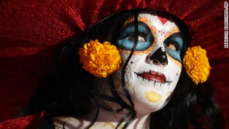 "A woman dressed as Mexico's iconic ""Catrina"" awaits the start of the Grand Procession of the Catrinas, part of upcoming Day of the Dead celebrations in Mexico City, Sunday, Oct. 22, 2017. The figure of a skeleton wearing an elegant broad-brimmed hat was first done as a satirical engraving by artist Jose Guadalupe Posada sometime between 1910 and his death in 1913. (AP Photo/Rebecca Blackwell)"