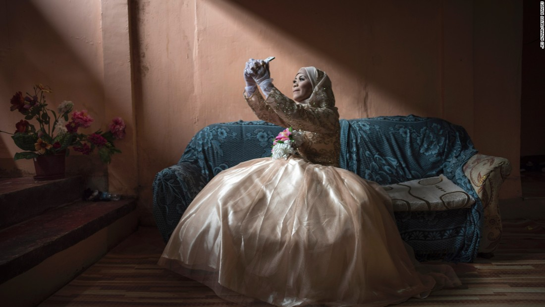 "Katty Malang Mikunug, a displaced resident of Marawi, Philippines, takes a photo of herself in her wedding dress Saturday, October 21, in Saguiaran, Philippines. A few days earlier, President Rodrigo Duterte announced that <a href=""http://www.cnn.com/2017/10/17/asia/duterte-marawi-liberation/index.html"" target=""_blank"">Marawi had been liberated</a> from ISIS-affiliated militants following a five-month standoff."