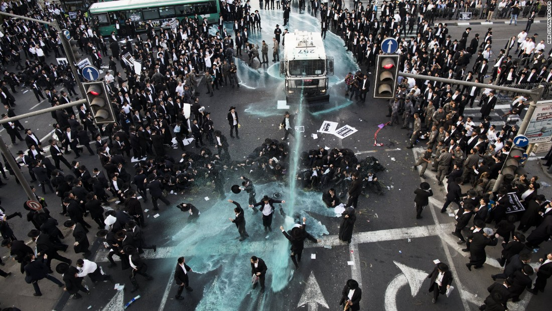 Police use a water cannon to disperse ultra-Orthodox Jews who were holding an anti-draft protest and blocking the main entrance to Jerusalem on Monday, October 23. Last month, the Israeli Supreme Court rejected a bill that would have exempted some ultra-Orthodox Jews from mandatory military service.