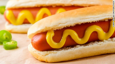 Traditional yummy hot dogs with mustard, close-up. Hot pepper, baking paper. Fast food and obesity.; Shutterstock ID 617277662; PO: Health