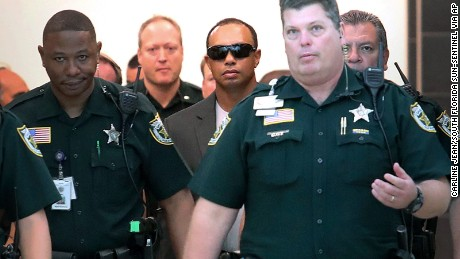 Golfer Tiger Woods, center right,  makes his way into a North County Courthouse courtroom in Palm Beach Gardens, Florida on Friday Oct. 27, 2017.