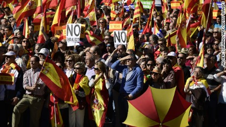 "People hold signs reading ""No to the coup"" while waving Spanish flags during a demonstration urging unity in Madrid on Saturday."