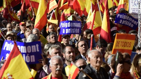 "TOPSHOT - People hold signs reading ""(Catalan regional president Carles) Puigdemont to prison""  while waving Spanish flags during a demonstration calling for unity at Plaza de Colon in Madrid on October 28, 2017, a day after direct control was imposed on Catalonia over a bid to break away from Spain. Spain moved to assert direct rule over Catalonia, replacing its executive and top functionaries to quash an independence drive that has plunged the country into crisis and unnerved secession-wary Europe. / AFP PHOTO / JAVIER SORIANOJAVIER SORIANO/AFP/Getty Images"
