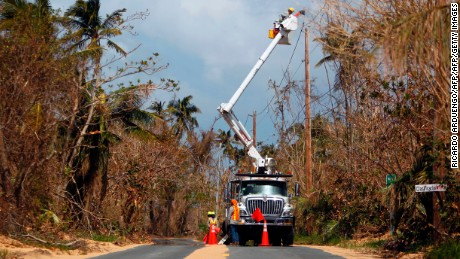 Puerto Rico Power Authority workers repair power lines in the aftermath of Hurricane Maria, in Loiza, Puerto Rico, September 28, 2017. The US island territory, working without electricity, is struggling to dig out and clean up from its disastrous brush with the hurricane, blamed for at least 33 deaths across the Caribbean. / AFP PHOTO / Ricardo ARDUENGO        (Photo credit should read RICARDO ARDUENGO/AFP/Getty Images)
