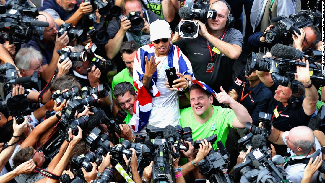 Hamilton poses for the cameras signaling his four world titles. How many more titles can the Briton win?